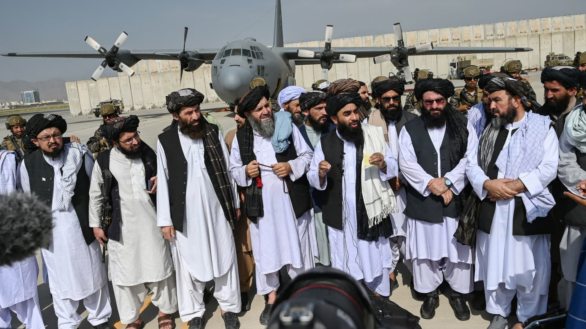 Taliban spokesman Zabihullah Mujahid (C, with shawl) speaks to the media at the airport in Kabul on August 31, 2021.