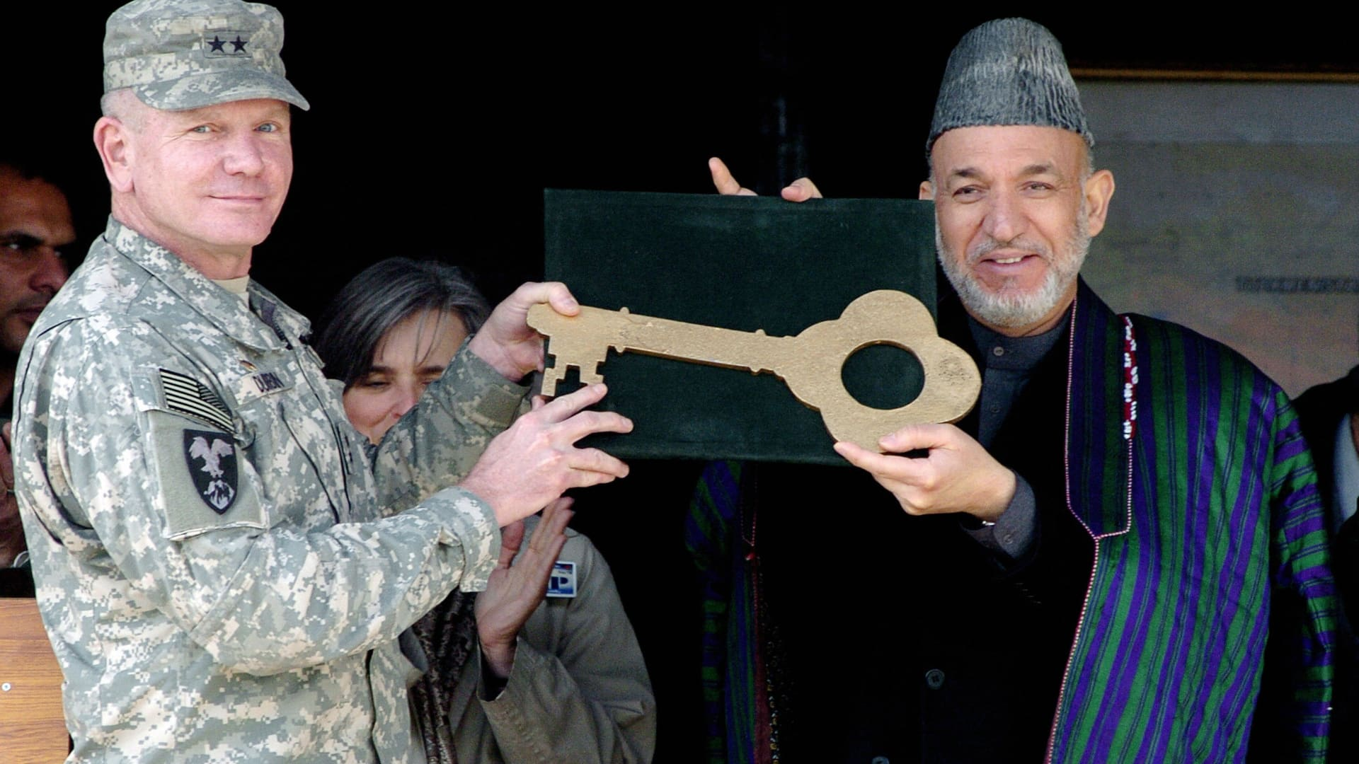 Kabul, AFGHANISTAN: Afghan President Hamid Karzai (R) receives a large key, representing the keys for military vehicles donated to the Afghan National Army, from commander of the Combined Security Transition Command in Afghanistan Major General Robert E. Durbin (L) during a weapons hand over ceremony in Kabul, 01 February 2007.