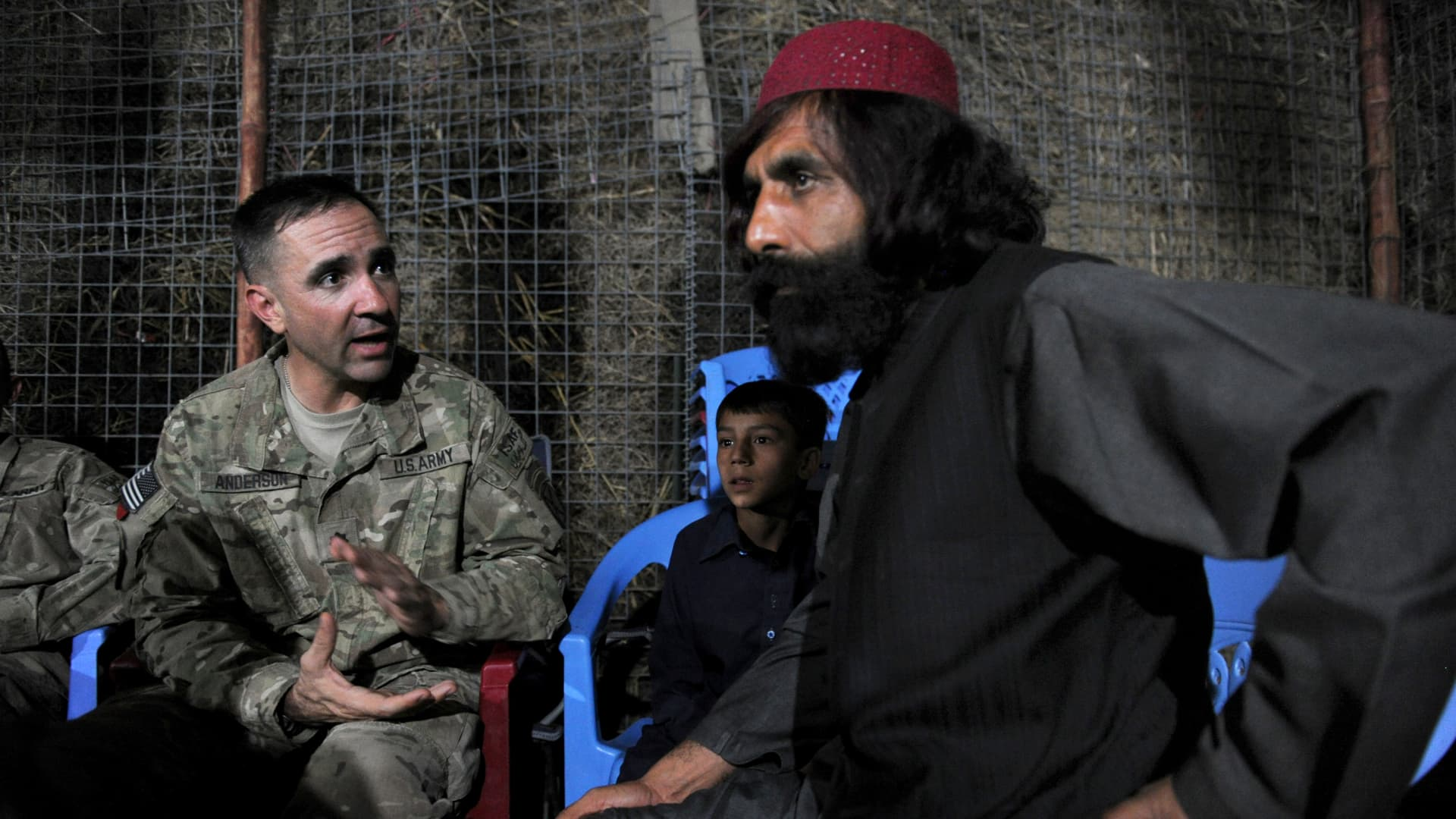 Afghan warlord Haji Tor Gani (R), hosts an iftar reception for US military officials belonging to 2nd Battalion, 87th Infantry Regiment, 3rd Brigade Combat Team, led by Lieutenant Colonel Gregory Anderson (L) in observance of Islam's holy month of Ramadan, at Tor Gani's highly secured compound in a village at Zahri distict in Afghanistan's southern Kandahar province, on August 11, 2011.