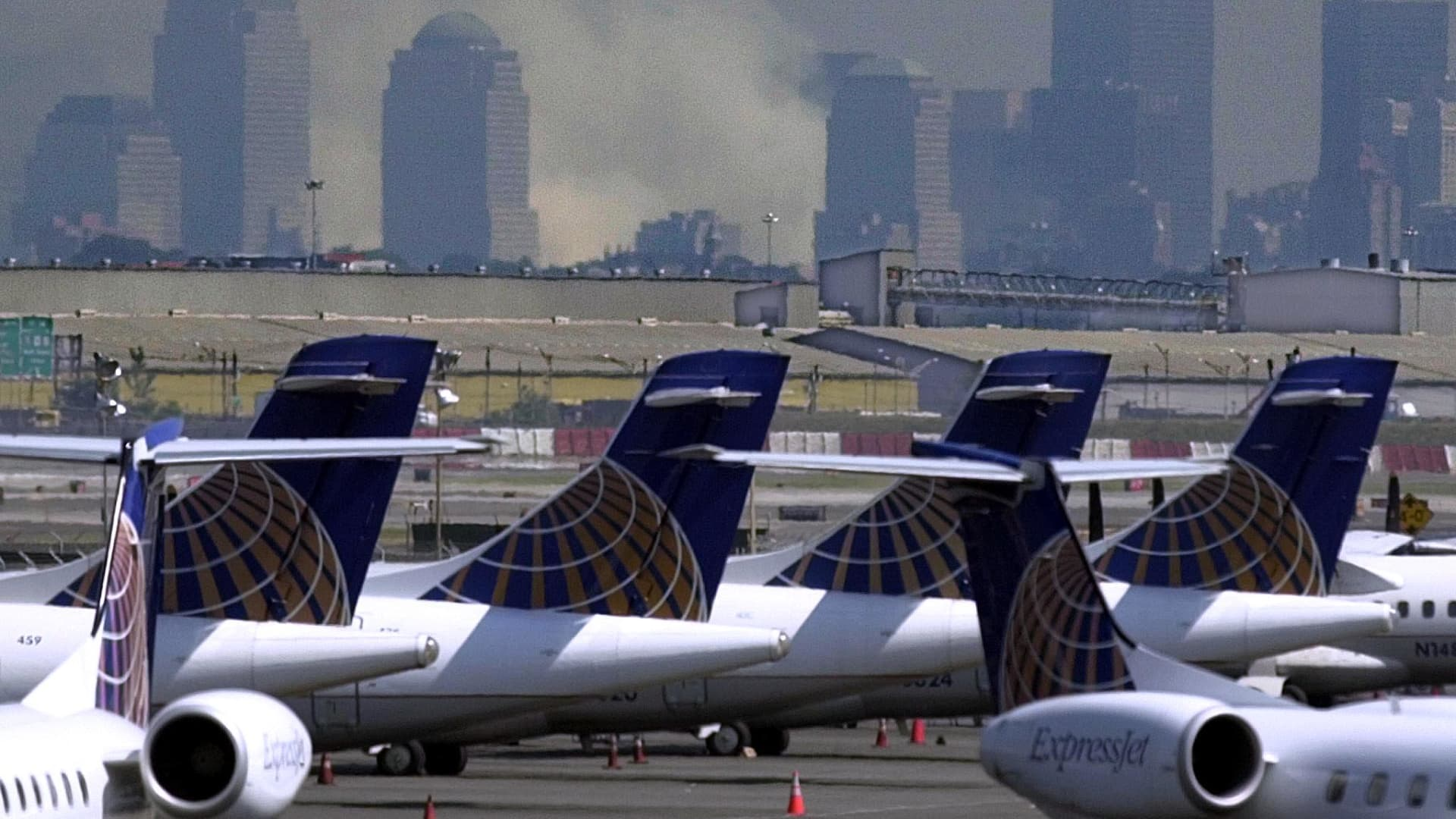 Smoke continues to billow from the remains of the World Trade Center as Continental Express planes sit at the closed Newark, New Jersey Airport 12 September 2001 in the wake of the terrorist attack on the World Trade Center. One of the hijacked planes departed the Newark Airport and later crashed near Pittsburgh, Pennsylvania.