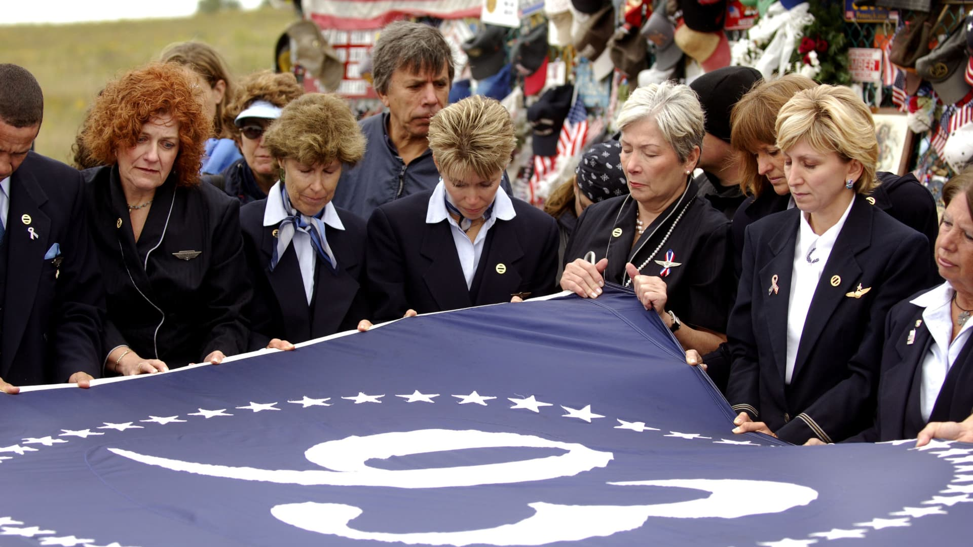 United Airlines flight attendants unfold a flag at a memorial site on the 5th anniversary of the September 11, 2001 attacks, where United Flight 93 crashed into a field in Shanksville, Pennsylvania, September 11, 2006.