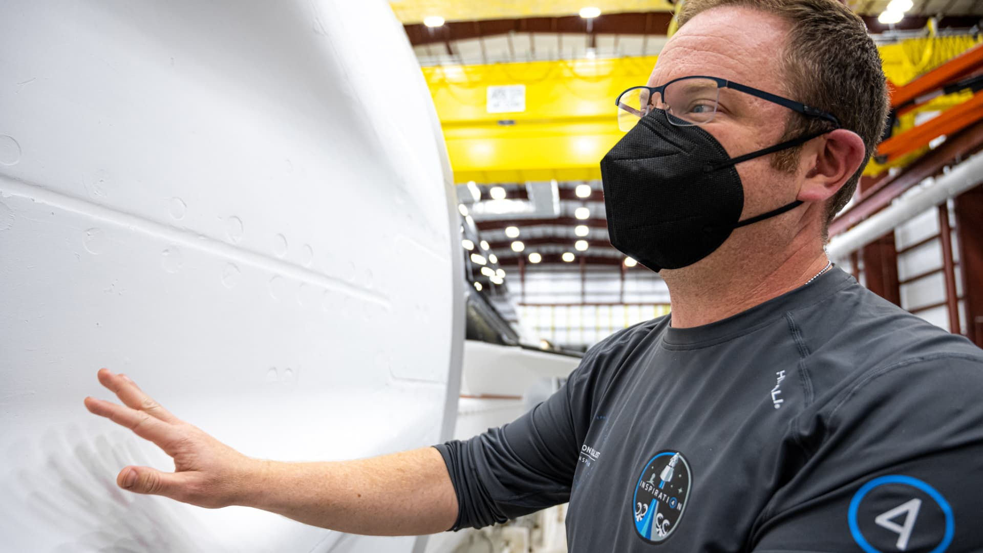 Chris Sembroski inspects the Crew Dragon capsule.