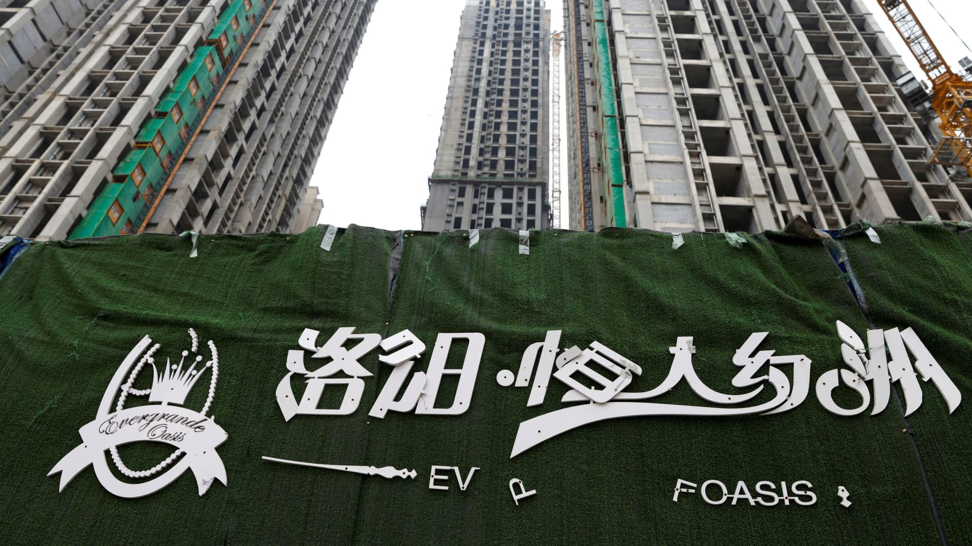 A peeling logo of the Evergrande Oasis, a housing complex developed by Evergrande Group, is pictured outside the construction site where the residential buildings stand unfinished, in Luoyang, China September 16, 2021. Picture taken September 16, 2021.