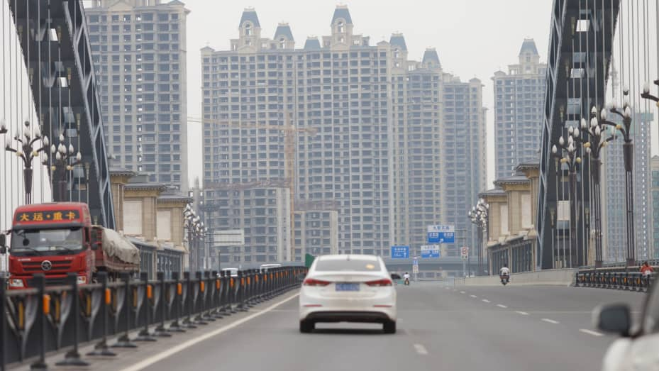 Vehicles drive near unfinished residential buildings from the Evergrande Oasis, a housing complex developed by Evergrande Group, in Luoyang, China September 16, 2021.