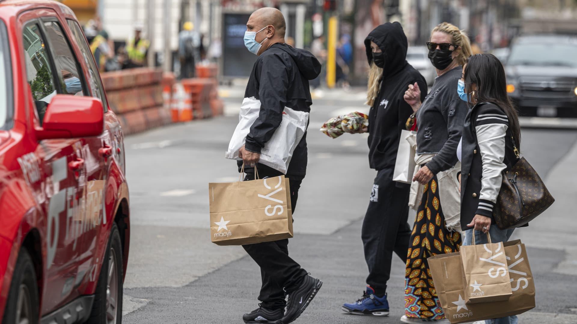 Pedestrians carry Macy's shopping bags in San Francisco, California, U.S., on Thursday, Sept. 16, 2021.