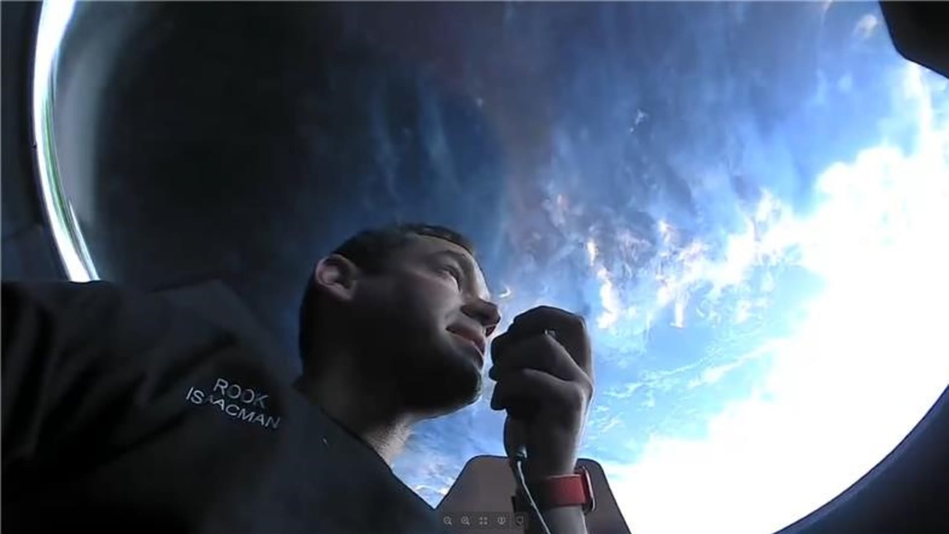 Spacecraft commander Jared Isaacman speaks into a microphone as he peers out the cupola window.