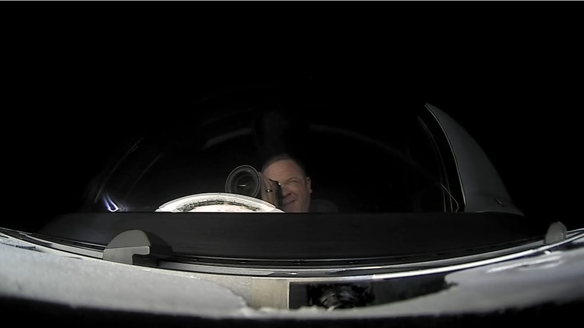 Mission specialist Chris Sembroski is seen taking a photo through the cupola, from an exterior camera on Crew Dragon.