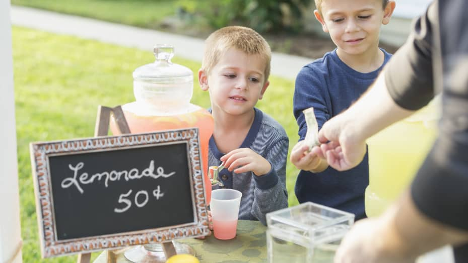 Two boys selling lemonade in their front yard. They are serving pink lemonade to a customer, cropped so only his arms are visible, he is handing cash to the older brother.