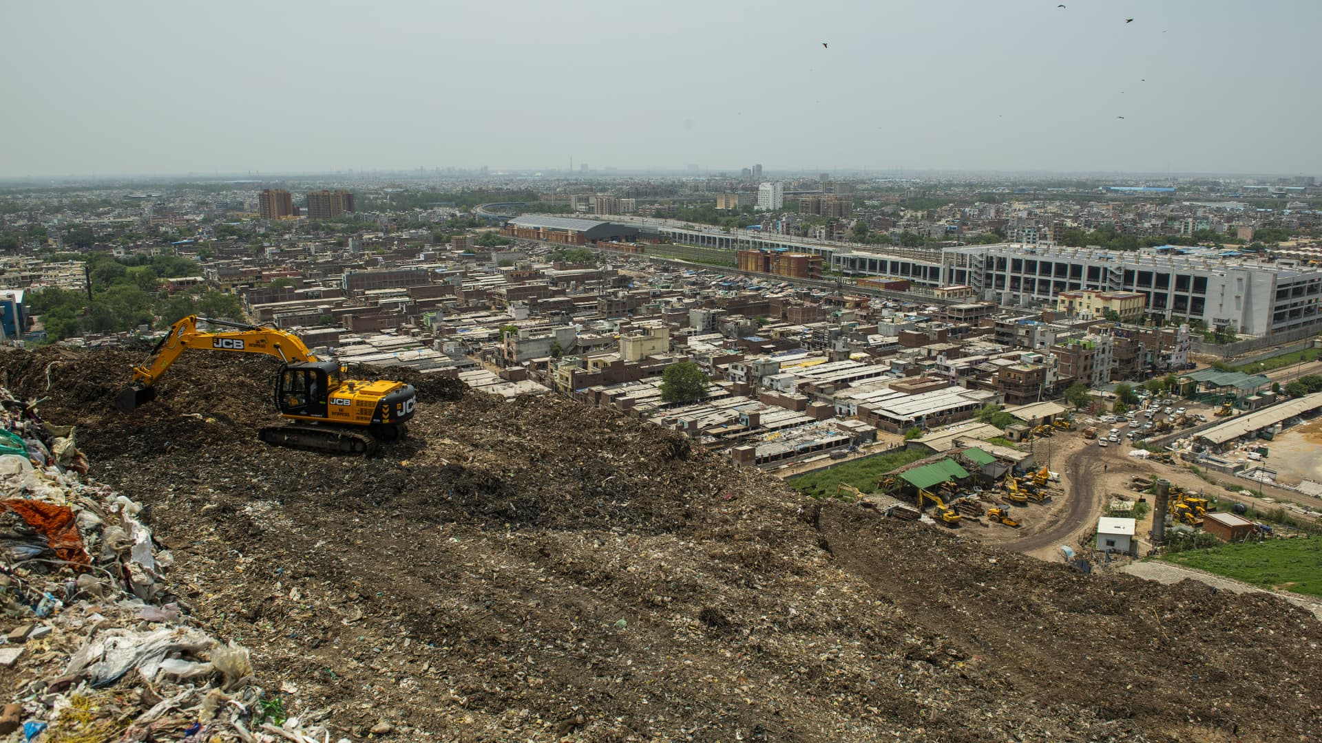 A machine picking up waste in the pile of garbage at the Ghazipur land fill site where city's daily waste has been dumped for last 35 years. The machine separates waste into three parts first stone and heavy concrete material second plastic, polythene and third is fertilizer and soils.
