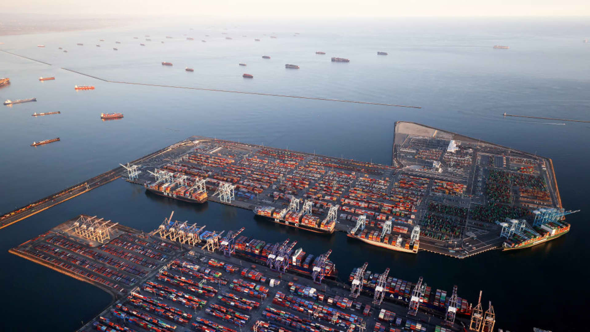 In an aerial view, container ships (Top L) are anchored by the ports of Long Beach and Los Angeles as they wait to offload on September 20, 2021 near Los Angeles, California.