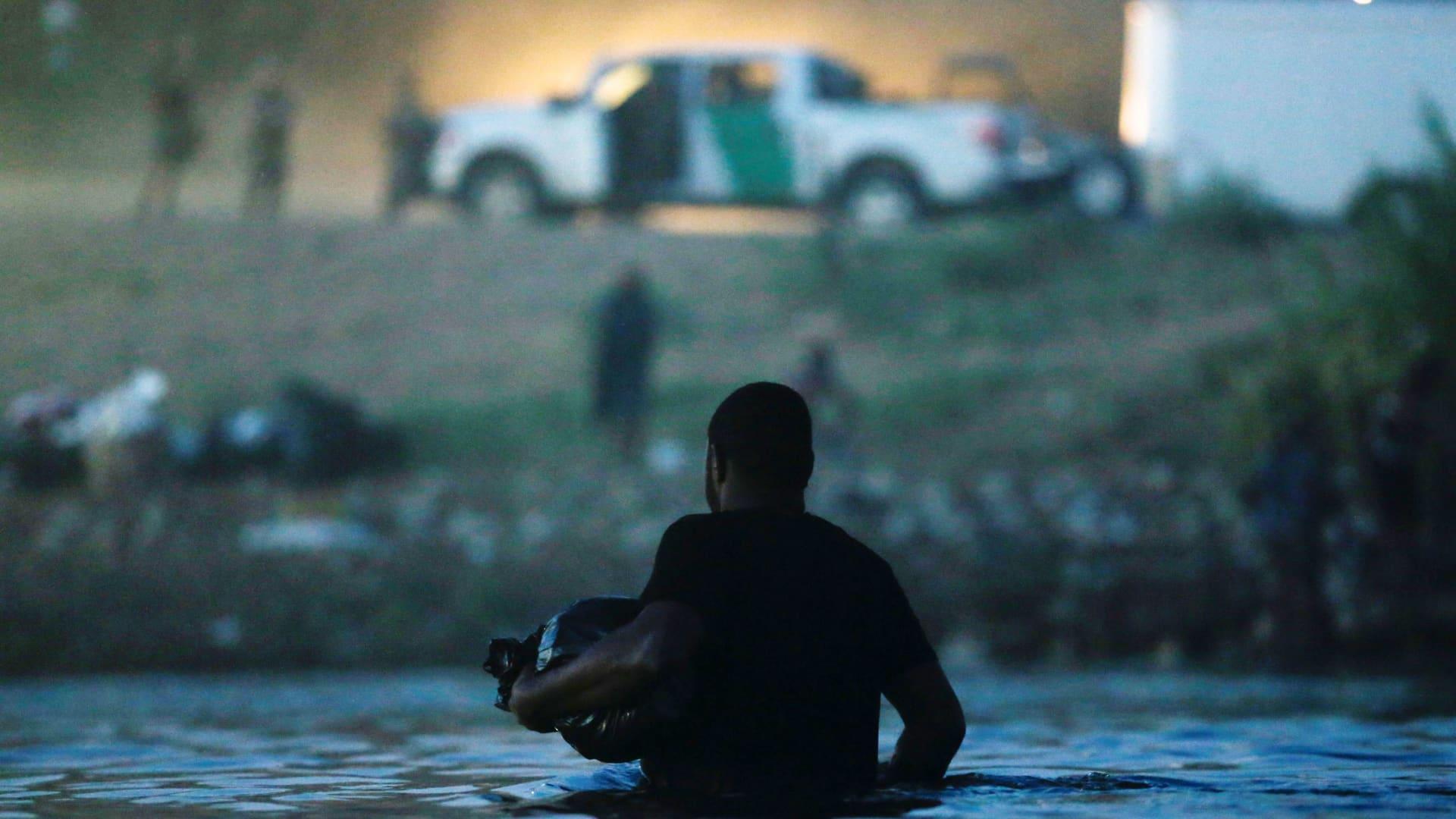 A migrant seeking refuge in the U.S. wades through the Rio Grande river from Ciudad Acuna, Mexico toward Del Rio, Texas, U.S. after getting supplies, in Ciudad Acuna, Mexico September 22, 2021.