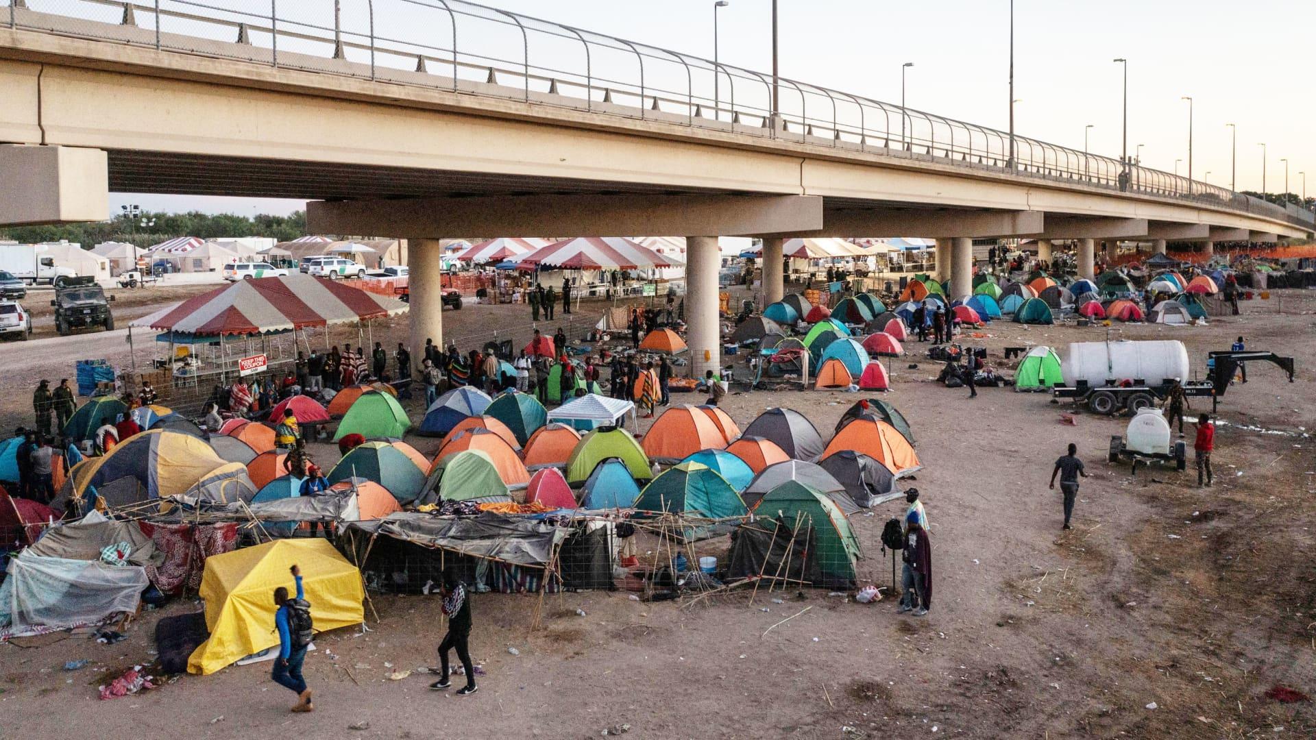Migrants walk through a makeshift border camp along the International Bridge in Del Rio, Texas, U.S. September 24, 2021.