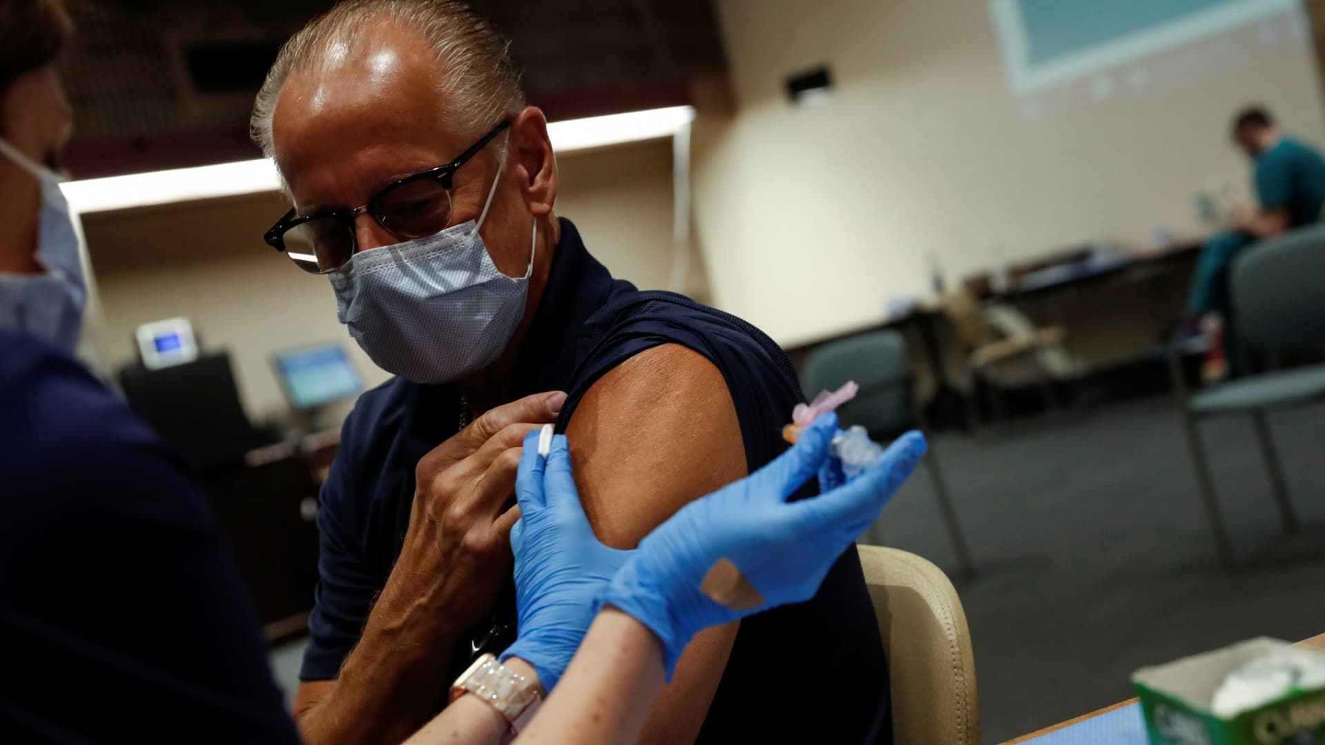 A registered nurse applies a dose of the Moderna COVID-19 vaccine to Sarasota Hospital worker Larry Hammers, 62, at the Sarasota Memorial Hospital in Sarasota, Florida, September 24, 2021.