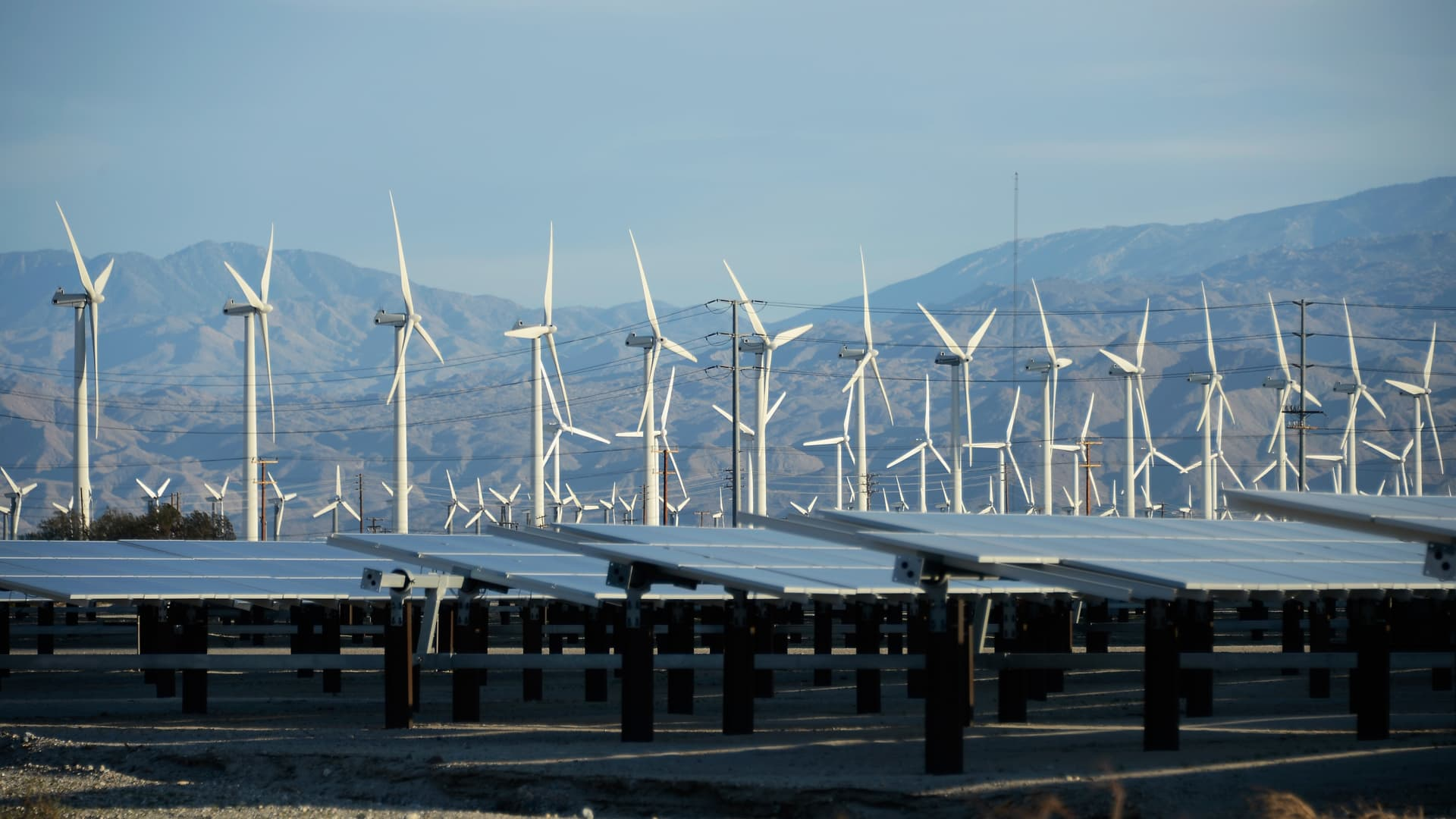 PALM SPRINGS, CA - MARCH 27:Giant wind turbines are powered by strong winds in front of solar panels on March 27, 2013 in Palm Springs, California. According to reports, California continues to lead the nation in green technology and has the lowest greenhouse gas emissions per capita, even with a growing economy and population.(Photo by Kevork Djansezian/Getty Images)