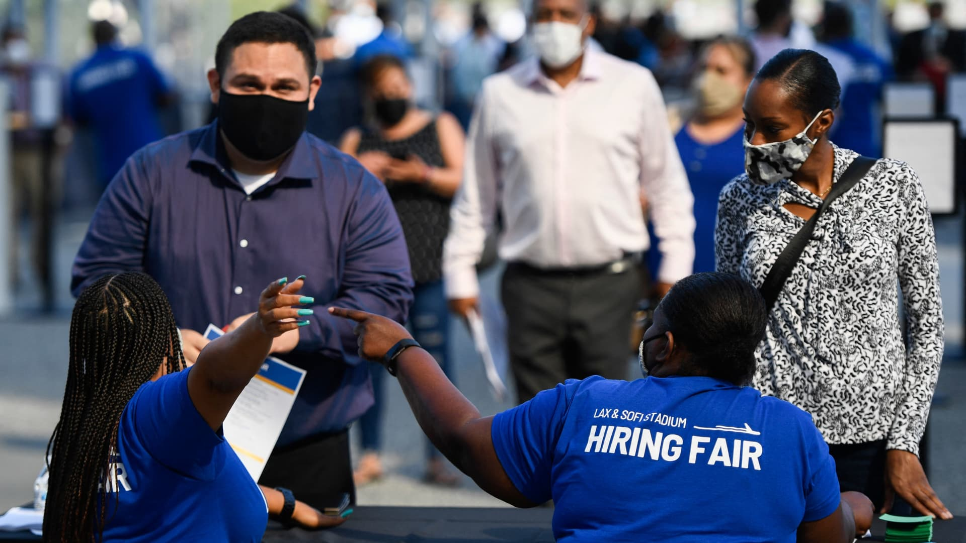 People receive information as they attend a job fair at SoFi Stadium on Sept. 9, 2021, in Inglewood, California.