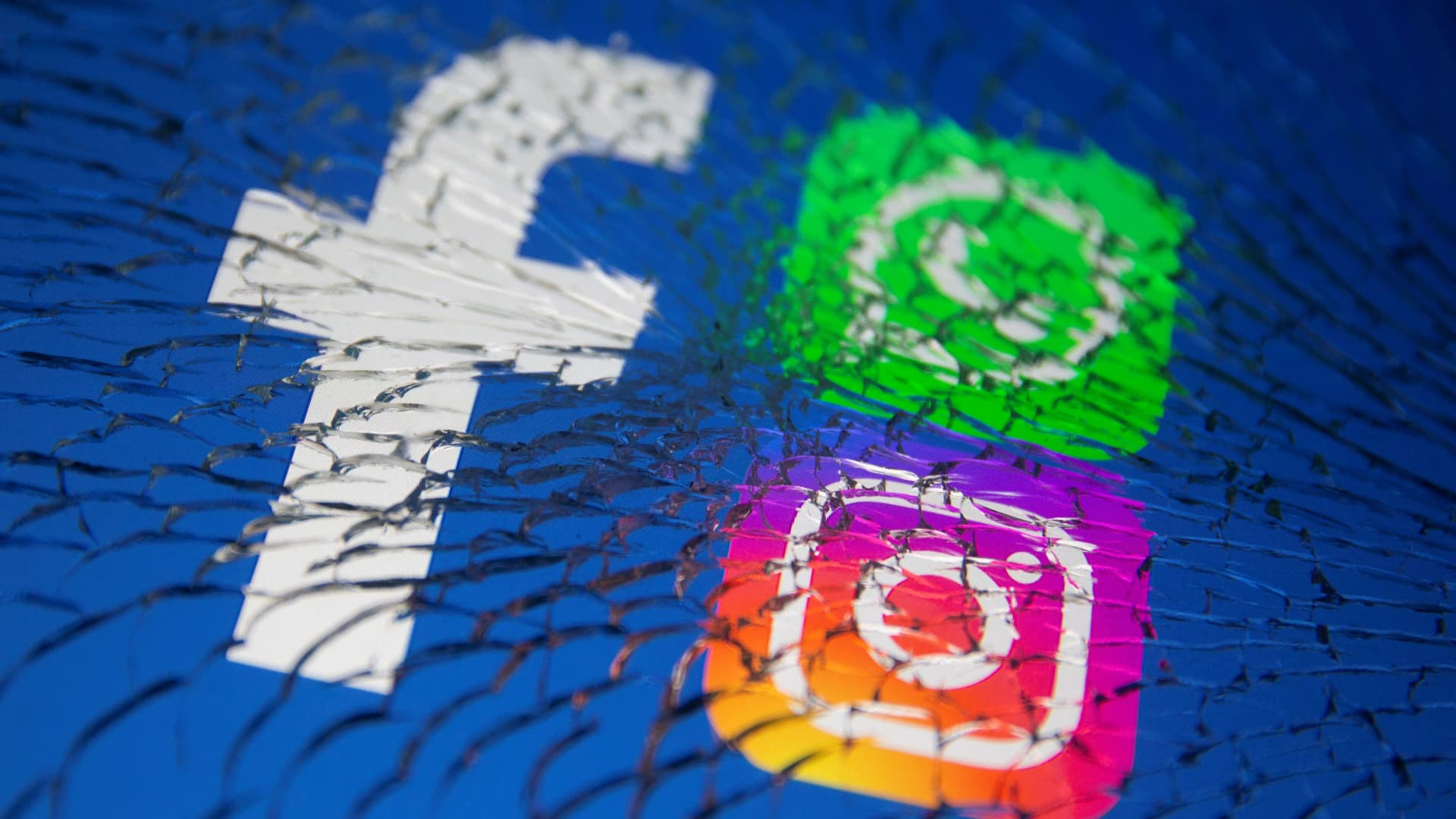 Facebook, Whatsapp and Instagram logos are displayed through broken glass in this illustration taken October 4, 2021.
