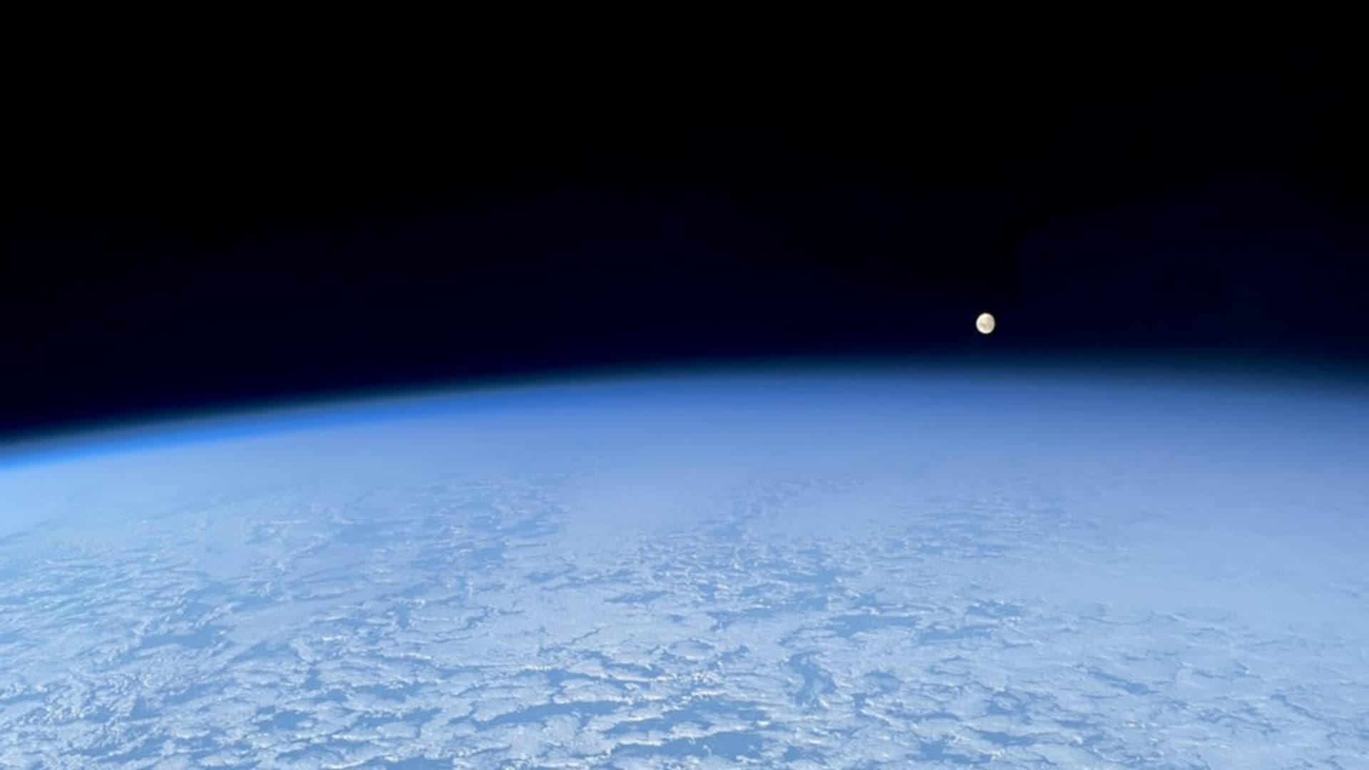 The moon rising in orbit above the edge of the Earth.