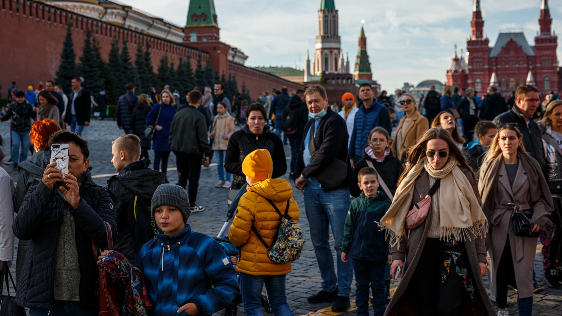 People walk through the Red Square in a sunny autumn day in Moscow on October 9, 2021.