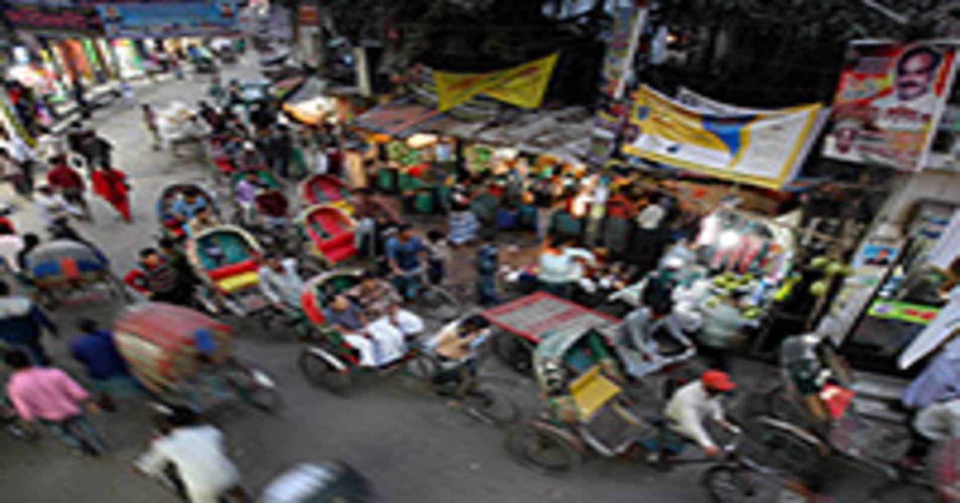 Pedestrians and rickshaws move along a street in the Old Market of Dhaka, Bangladesh.