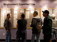 People check the jobs board at a Denver Workforce Center, part of the Denver Office of Economic Development, in Denver, Colorado, U.S.